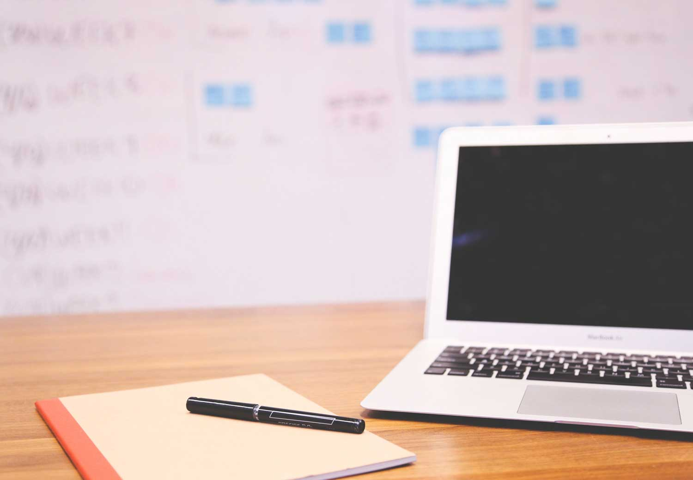 Scrivania con mac e progetto sullo sfondo